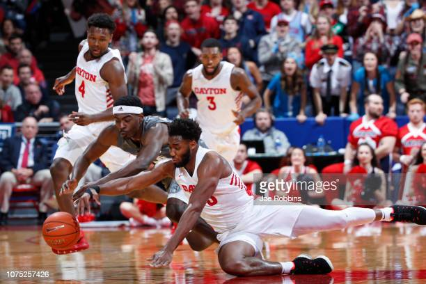 Josh Cunningham of the Dayton Flyers battles for a loose ball against Aric Holman of the Mississippi State Bulldogs in the second half of the game at...