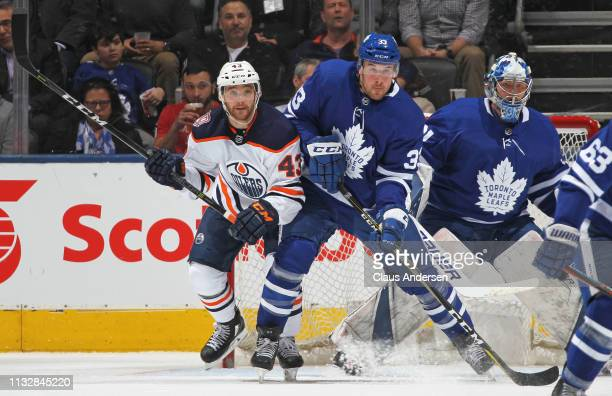 Josh Currie of the Edmonton Oilers battles against Frederik Gauthier of the Toronto Maple Leafs during an NHL game at Scotiabank Arena on February 27...