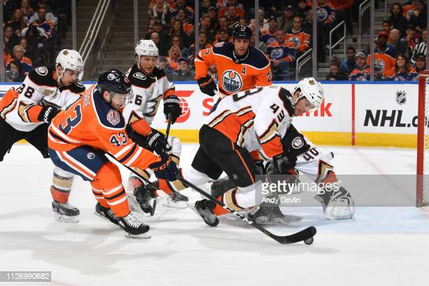 Josh Currie of the Edmonton Oilers shoots the puck past Jaycob Megna and Kevin Boyle of the Anaheim Ducks on February 23 2019 at Rogers Place in...