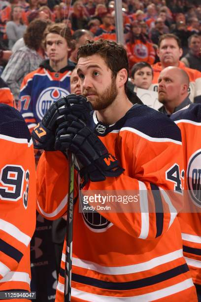 Josh Currie of the Edmonton Oilers stands for the singing of the national anthem prior to the game against the Arizona Coyotes on February 19 2019 at...