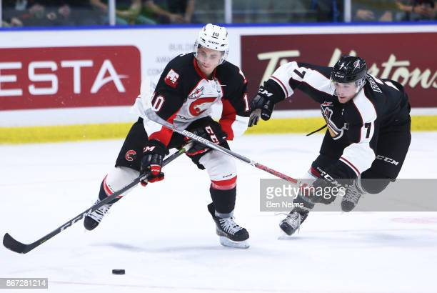 Josh Curtis of the Prince George Cougars skates with the puck against Ty Ronning of the Vancouver Giants during the third period of their WHL game at...