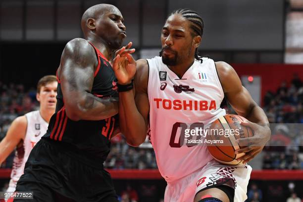 Josh Davis of the Kawasaki Brave Thunders handles the ball under pressure from Jawad Williams of the Alvark Tokyo during the BLeague match between...