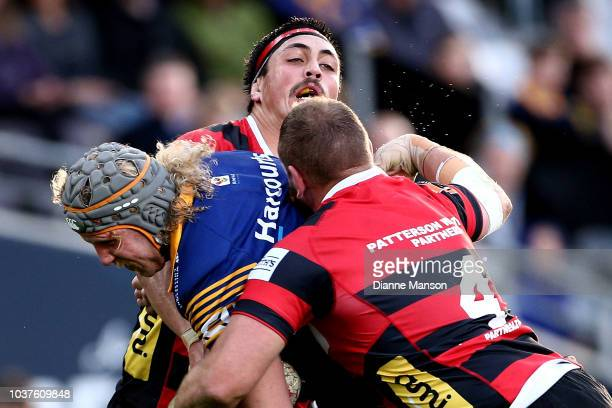 Josh Dickson of Otago is tackled by Daniel LienertBrown and Luke Romano of Canterbury during the round six Mitre 10 Cup match between Otago and...