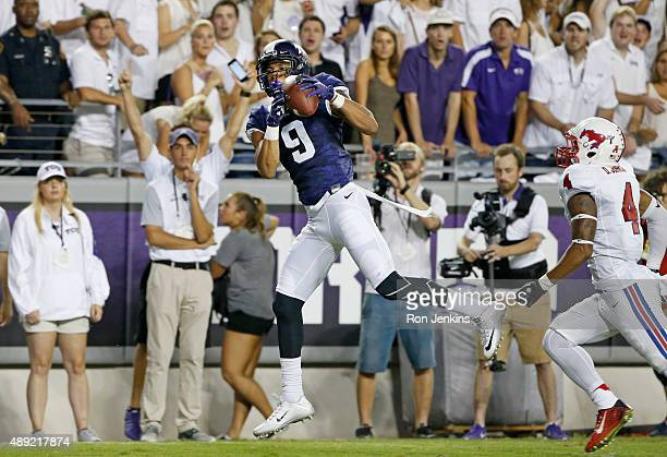Josh Doctson of the TCU Horned Frogs catches a touchdown pass as David Johnson of the Southern Methodist Mustangs looks on in the second quarter at...