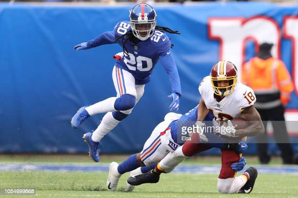 Josh Doctson of the Washington Redskins takes a hit by Tae Davis of the New York Giants as Janoris Jenkins defends during the second quarter at...