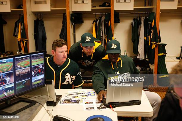 Josh Donaldson Craig Gentry and Hitting Coach Chili Davis of the Oakland Athletics study at bats in the clubhouse during the game against the San...