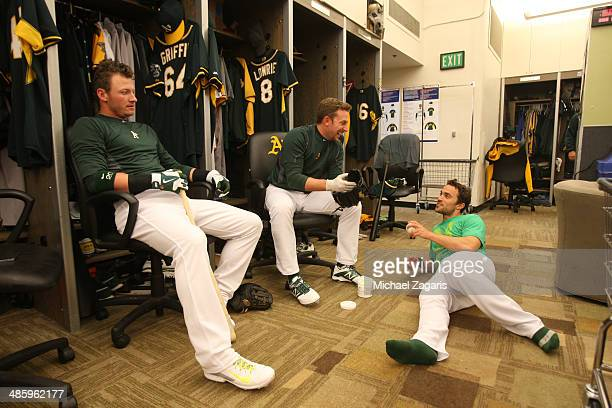 Josh Donaldson Jed Lowrie and Sam Fuld of the Oakland Athletics relax in the clubhouse prior to the game against the Seattle Mariners being cancelled...