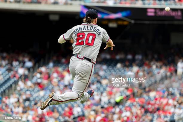 Josh Donaldson of the Atlanta Braves makes a leaping throw to first base against the Washington Nationals during the third inning at Nationals Park...