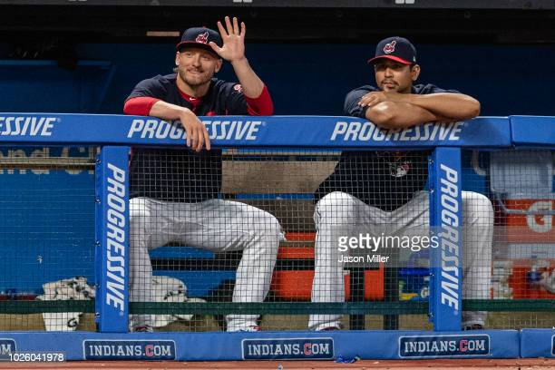 Josh Donaldson of the Cleveland Indians joins Carlos Carrasco on the bench and waves to the Tampa Bay Rays bench during the fifth inning at...