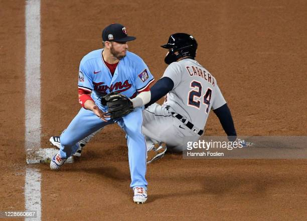 Josh Donaldson of the Minnesota Twins gets Miguel Cabrera of the Detroit Tigers out a third base to complete a double play during the fourth inning...