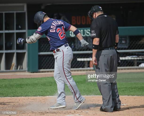 Josh Donaldson of the Minnesota Twins kicks dirt on umpire Dan Bellino after hitting a home run following an argument over a called strike in the 6th...