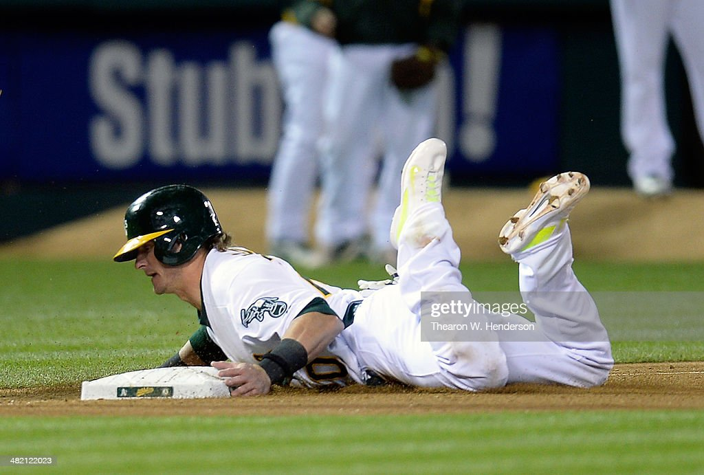 Josh Donaldson #20 of the Oakland Athletics dives into third base safe, reaching from second base on a wild pitch by Cleveland Indians pitcher Bryan Shaw #27 in the bottom or the seventh inning at O.co Coliseum on April 2, 2014 in Oakland, California. Donaldson later scored on an RBI single from Brandon Moss.