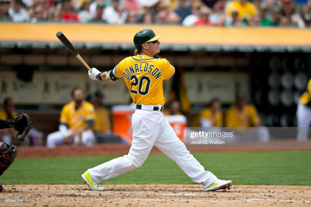Josh Donaldson #20 of the Oakland Athletics hits a sacrifice fly ball for an RBI against the Baltimore Orioles during the third inning at O.co Coliseum on July 20, 2014 in Oakland, California. The Oakland Athletics defeated the Baltimore Orioles 10-2.