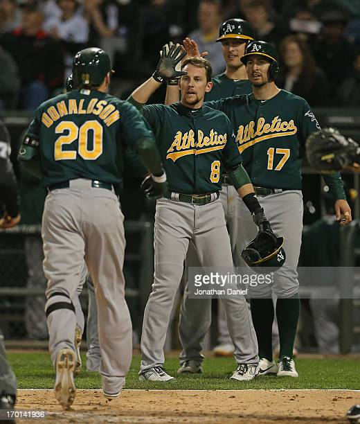 Josh Donaldson of the Oakland Athletics is greeted by Jed Lowrie Adam Rosales and Nate Freiman after hitting a grand slam home run in the 6th inning...