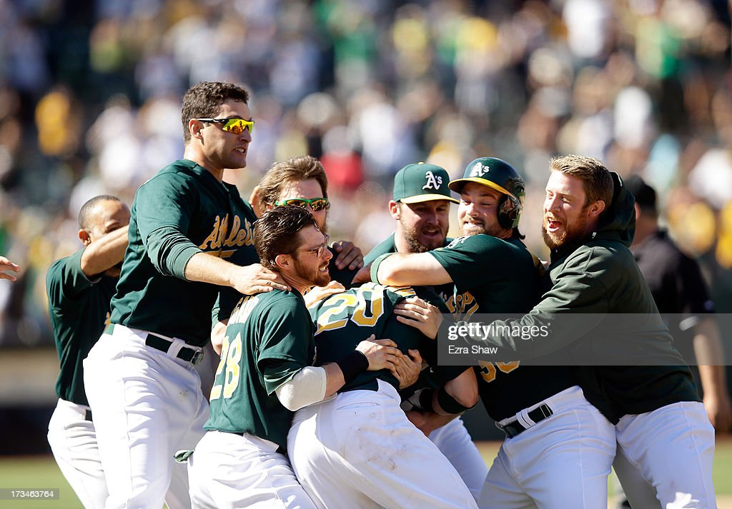 Josh Donaldson #20 of the Oakland Athletics is mobbed by teammates after Donaldson hit the game-winning hit in the 11th inning that scored Chris Young #25 to beat the Boston Red Sox at O.co Coliseum on July 14, 2013 in Oakland, California.