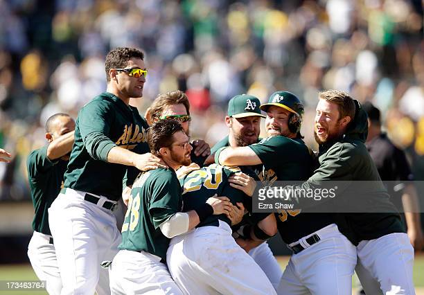 Josh Donaldson of the Oakland Athletics is mobbed by teammates after Donaldson hit the gamewinning hit in the 11th inning that scored Chris Young to...