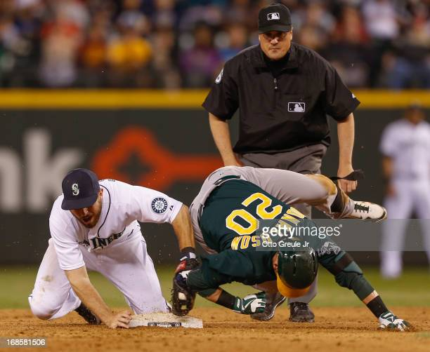 Josh Donaldson of the Oakland Athletics is tagged out by second baseman Dustin Ackley of the Seattle Mariners as he tries to stretch a single into a...