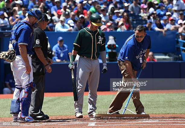 Josh Donaldson of the Oakland Athletics requests groundscrew maintenance from groundscrew worker Tom Farrell in the first inning during MLB game...