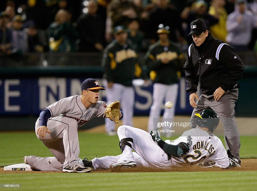 Josh Donaldson #20 of the Oakland Athletics slides safely into third base for a triple in the eighth inning while Matt Dominguez #30 of the Houston Astros waits for the ball at O.co Coliseum on April 16, 2013 in Oakland, California. Donaldson's triple scored Josh Reddick #16 to give the Athletics a 4-3 lead.