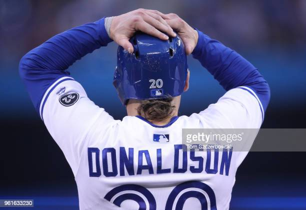 Josh Donaldson of the Toronto Blue Jays adjusts his helmet as he waits on first base during an injury delay in the third inning during MLB game...