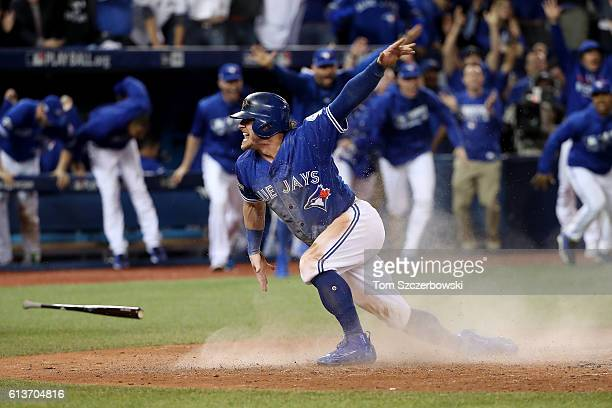 Josh Donaldson of the Toronto Blue Jays celebrates after sliding safely into home plate in the tenth inning for the Toronto Blue Jays to defeat the...