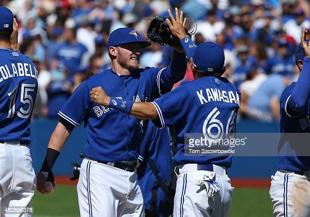 Josh Donaldson of the Toronto Blue Jays celebrates their victory with Munenori Kawasaki during MLB game action against the Minnesota Twins on August...