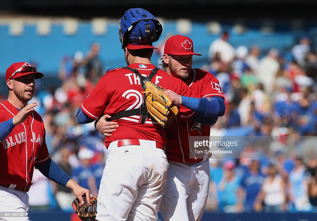 Josh Donaldson #20 of the Toronto Blue Jays celebrates their victory with Josh Thole #22 who was designated for assignment following their game during MLB game action against the Minnesota Twins on August 28, 2016 at Rogers Centre in Toronto, Ontario, Canada.