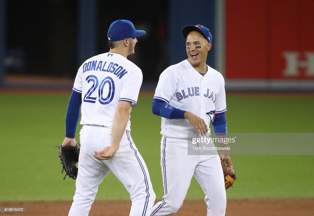 Josh Donaldson #20 of the Toronto Blue Jays celebrates their victory with Ryan Goins #17 during MLB game action against the Houston Astros at Rogers Centre on July 6, 2017 in Toronto, Canada.