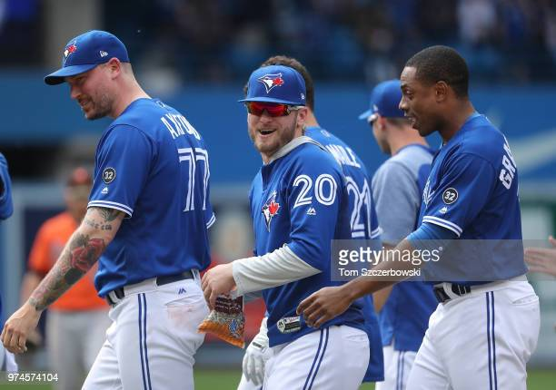 Josh Donaldson of the Toronto Blue Jays celebrates their victory with John Axford and Curtis Granderson in the tenth inning during MLB game action...