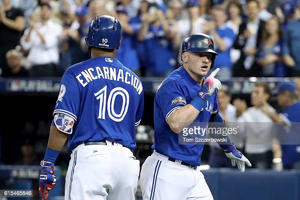 Josh Donaldson of the Toronto Blue Jays celebrates with teammate Edwin Encarnacion after hitting a solo home run in the third inning against Corey...