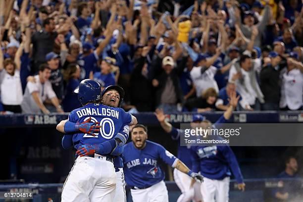 Josh Donaldson of the Toronto Blue Jays celebrates with teammate Troy Tulowitzki after the Toronto Blue Jays defeated the Texas Rangers 76 in ten...