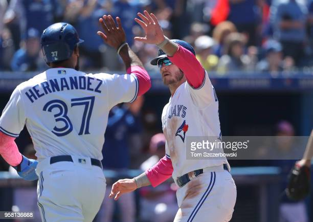 Josh Donaldson of the Toronto Blue Jays celebrates with Teoscar Hernandez after both runners scored on a tworun double by Justin Smoak in the fifth...