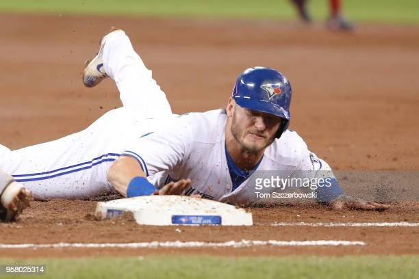 Josh Donaldson of the Toronto Blue Jays dives back to first base safely on a pickoff attempt in the first inning during MLB game action against the...