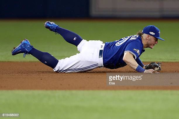 Josh Donaldson of the Toronto Blue Jays dives to field the ball hit by Carlos Santana of the Cleveland Indians in the fifth inning during game four...