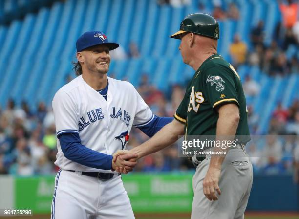Josh Donaldson of the Toronto Blue Jays greets former third baseman and third base coach Matt Williams of the Oakland Athletics as they shake hands...