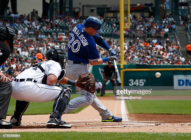 Josh Donaldson of the Toronto Blue Jays hits an RBI single in the first inning in front of catcher James McCann of the Detroit Tigers at Comerica...