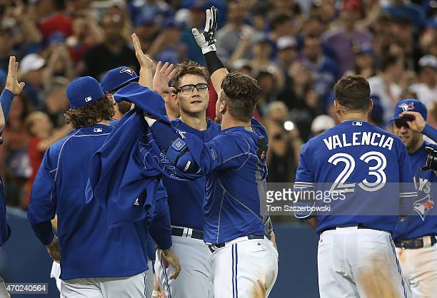 Josh Donaldson of the Toronto Blue Jays is congratulated by Brett Cecil after hitting a gamewinning home run in the tenth inning during MLB game...