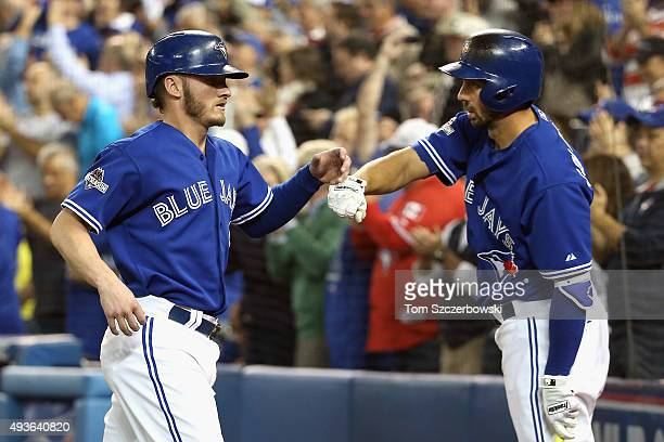 Josh Donaldson of the Toronto Blue Jays is congratulated by Chris Colabello of the Toronto Blue Jays after scoring a run in the seventh inning...