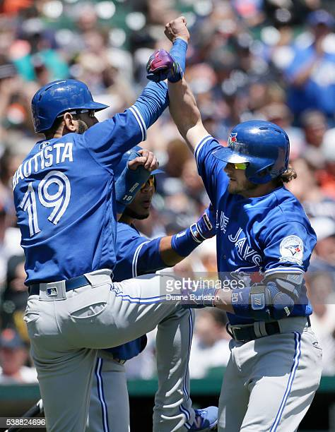 Josh Donaldson of the Toronto Blue Jays is congratulated by Jose Bautista of the Toronto Blue Jays and Edwin Encarnacion of the Toronto Blue Jays...
