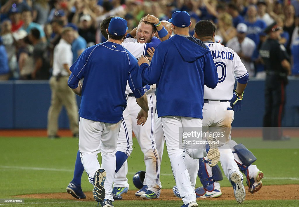 Josh Donaldson #20 of the Toronto Blue Jays is congratulated by teammates after his game-winning RBI single in the eleventh inning during MLB game action against the Kansas City Royals on July 31, 2015 at Rogers Centre in Toronto, Ontario, Canada.