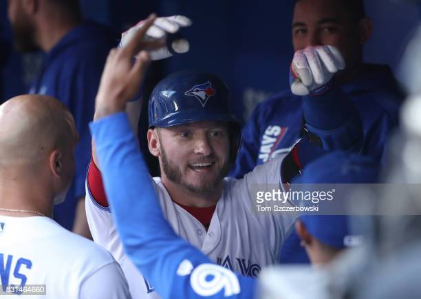 Josh Donaldson of the Toronto Blue Jays is congratulated by teammates in the dugout after hitting a tworun home run in the first inning during MLB...