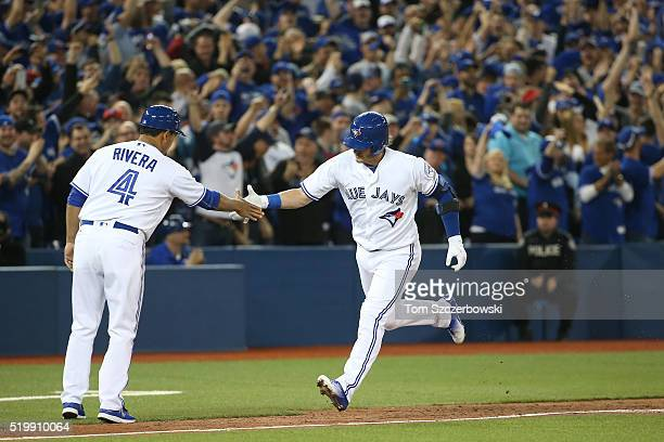 Josh Donaldson of the Toronto Blue Jays is congratulated by third base coach Luis Rivera after hitting a grand slam home run in the fourth inning...