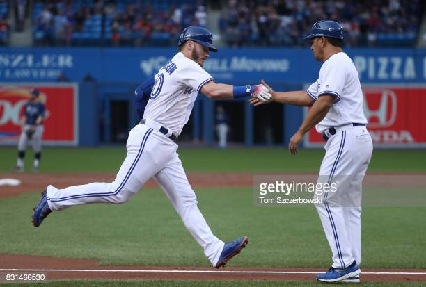 Josh Donaldson of the Toronto Blue Jays is congratulated by third base coach Luis Rivera after hitting a tworun home run in the first inning during...