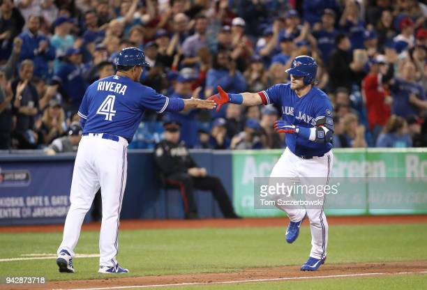 Josh Donaldson of the Toronto Blue Jays is congratulated by third base coach Luis Rivera after hitting a solo home run in the sixth inning during MLB...