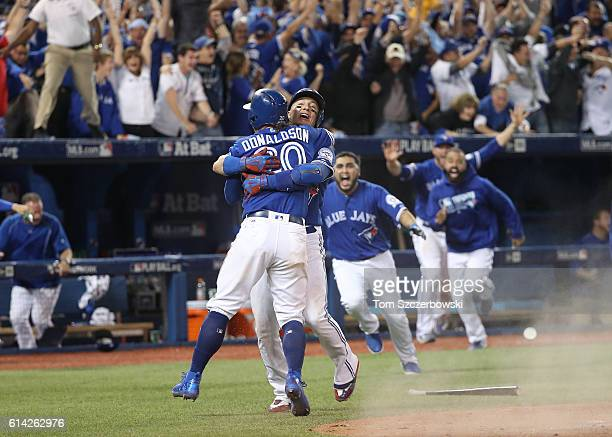 Josh Donaldson of the Toronto Blue Jays is congratulated by Troy Tulowitzki after scoring the gamewinning run in the tenth inning during MLB game...