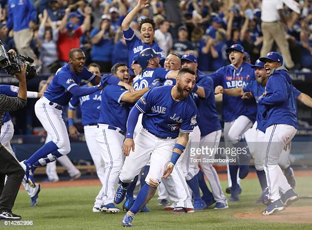 Josh Donaldson of the Toronto Blue Jays is congratulated by Troy Tulowitzki after scoring the gamewinning run as Kevin Pillar runs while celebrating...