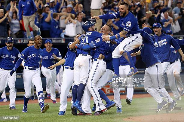 Josh Donaldson of the Toronto Blue Jays is swarmed by his teammates after the Toronto Blue Jays defeated the Texas Rangers 76 in ten innings for game...