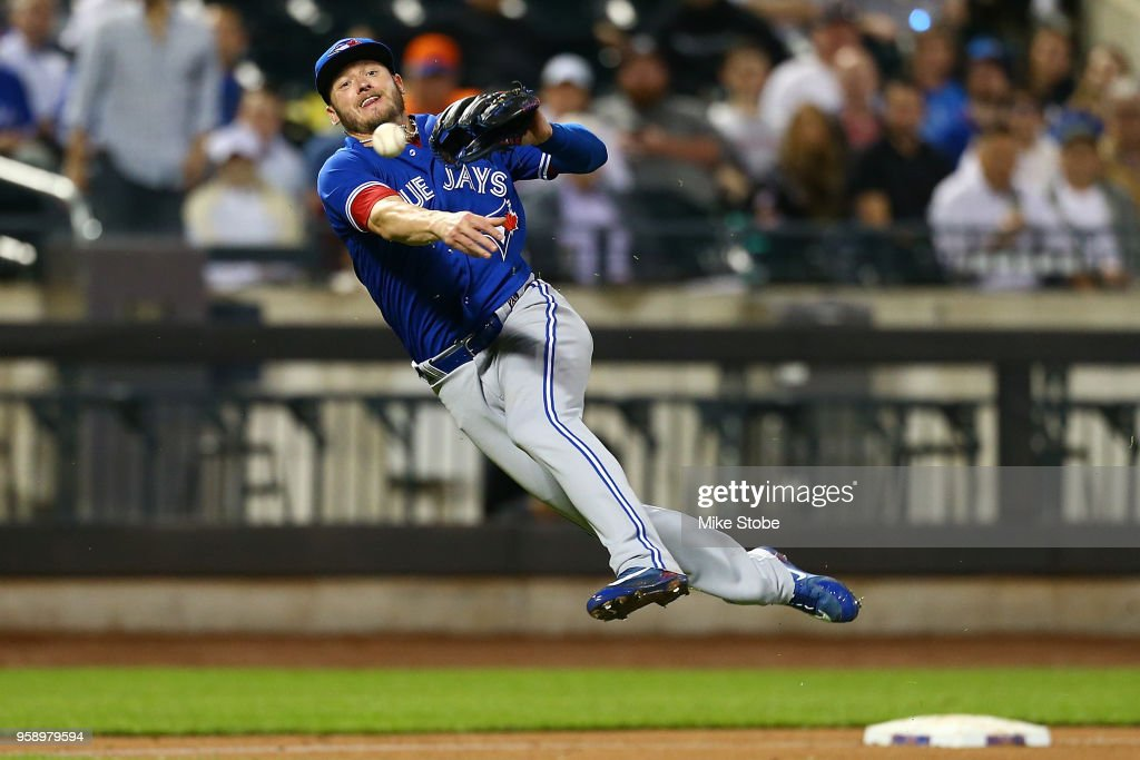 Josh Donaldson #20 of the Toronto Blue Jays is unable to throw out Juan Lagares #12 of the New York Mets in the fifth inning at Citi Field on May 15, 2018 in the Flushing neighborhood of the Queens borough of New York City.