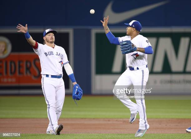 Josh Donaldson of the Toronto Blue Jays playfully tosses the ball back to Marcus Stroman after Stroman made a play to throw out the baserunner in the...