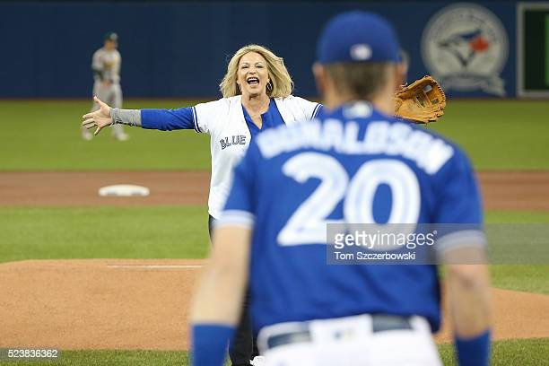 Josh Donaldson of the Toronto Blue Jays prepares to hug his mother Lisa French after she threw out the first pitch before the start of MLB game...